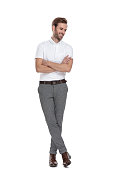 istock young casual man standing with hands crossed and looks down 1131988446