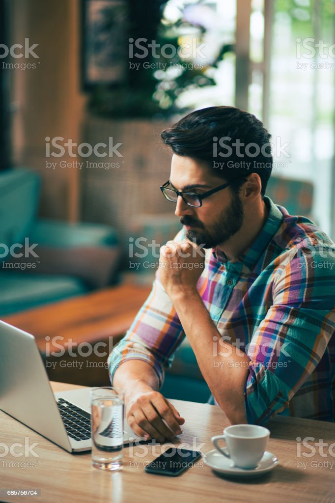 Young  casual man using laptop in modern cafe. foto stock royalty-free