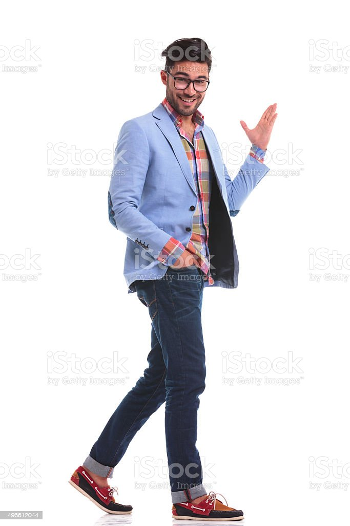 young casual man walking while presenting something stock photo
