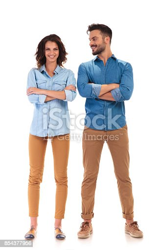 istock young casual man with hands crossed looks at his girlfriend 854377956