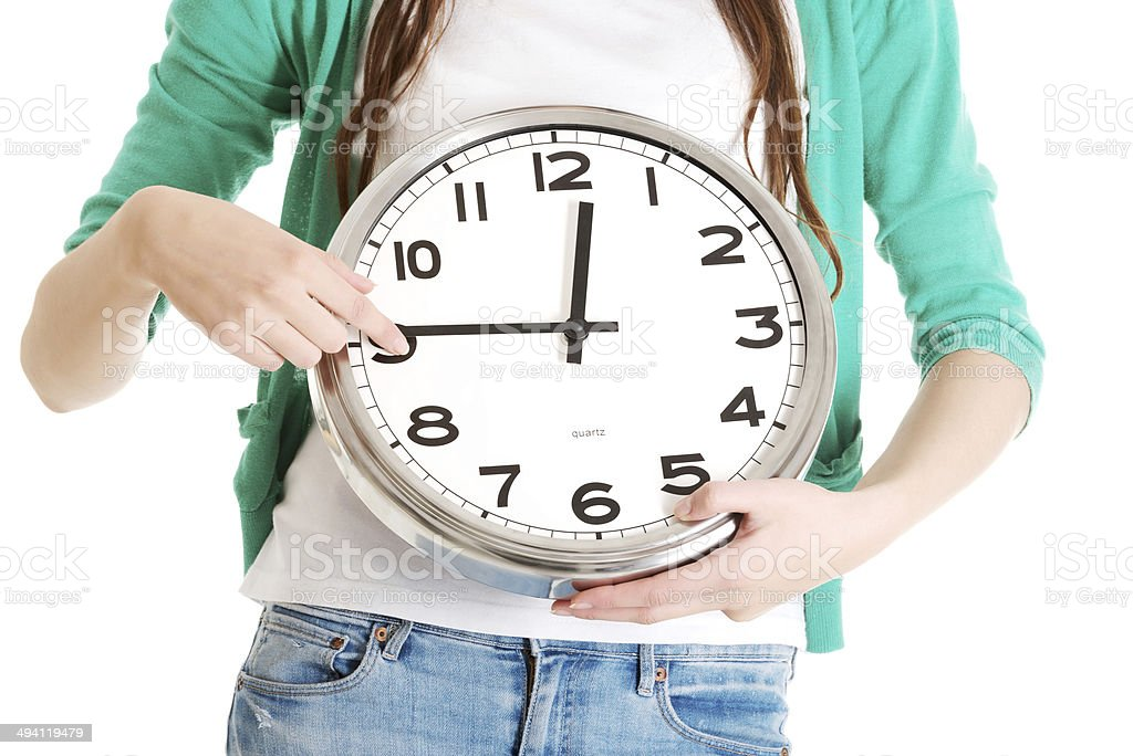 Young casual woman holding clock. stock photo