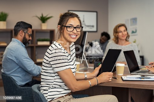 Beautiful latin businesswoman looking at camera and smiling while working in office. Cheerful young woman wearing spectacles and holding digital tablet. Creative girl working with colleagues at agency.