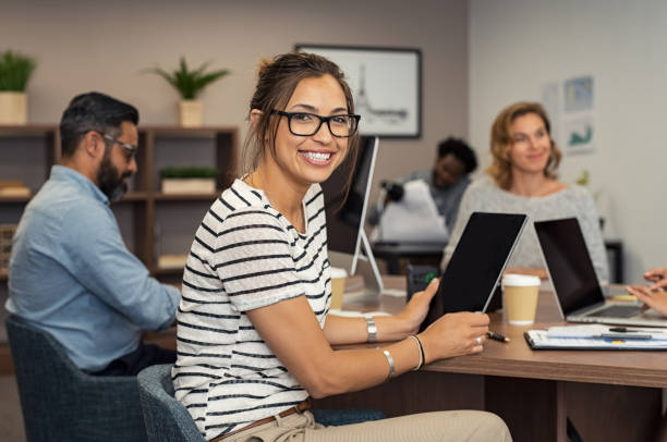 Young casual woman working Beautiful latin businesswoman looking at camera and smiling while working in office. Cheerful young woman wearing spectacles and holding digital tablet. Creative girl working with colleagues at agency. apprentice stock pictures, royalty-free photos & images