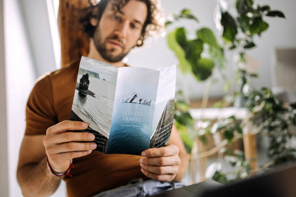Young casually clothed man looking at travel flyer in his apartment stock photo