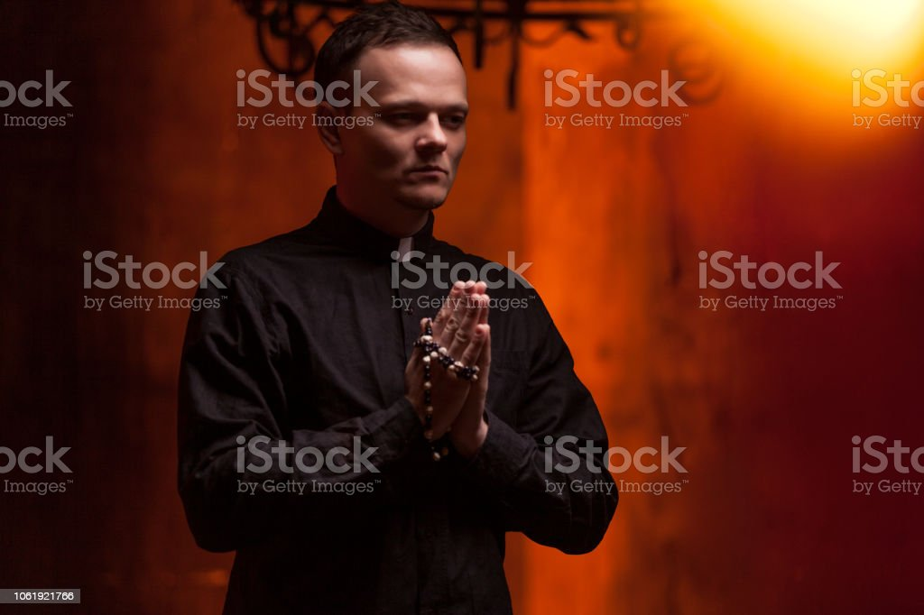 Young Catholic Praying priest. Portrait of priest Next to the candles prays with his hands folded near the face. Red wall on the background. Indoor handsome portrait of religion man stock photo