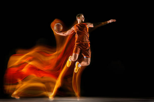 Young caucasian basketball player against dark background in mixed light stock photo