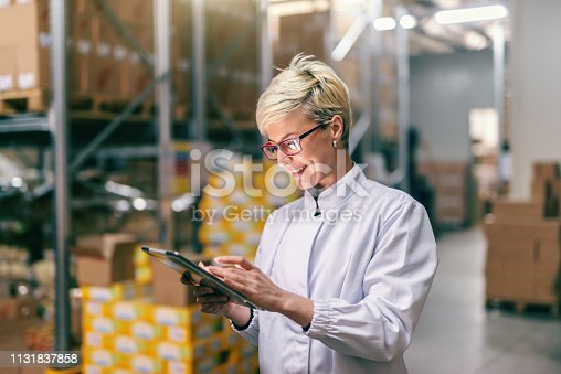 Young Caucasian blonde woman in white uniform using tablet in warehouse.