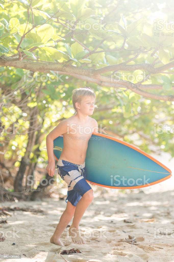 Young Caucasian boy heads out to go surfing royalty-free stock photo