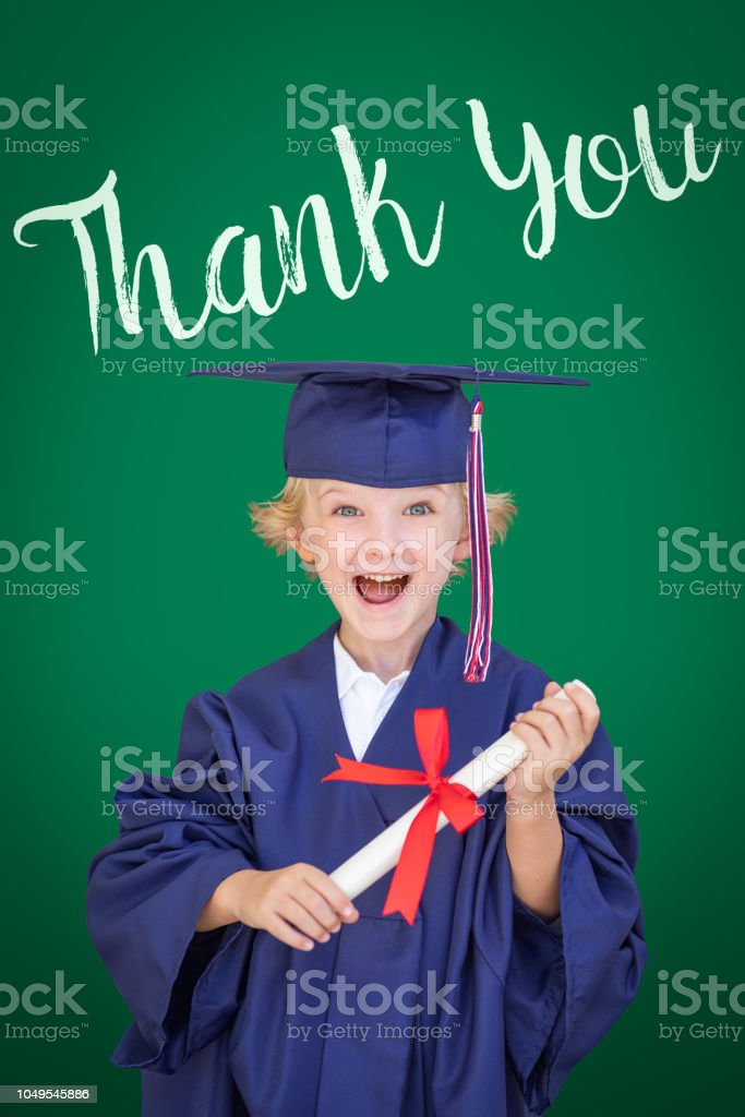 Young Caucasian Boy In Graduation Cap and Gown Against Green Chalkboard Background With Thank You stock photo