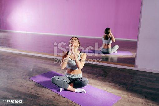 Young Caucasian brunette in sportswear sitting on the mat in gym and doing exercises for neck. In background mirror. The best workouts are the ones we do everyday.