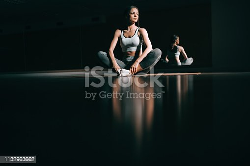 istock Young Caucasian brunette sitting on the mat in dark and looking away. Fitness studio interior, in background mirror. 1132963662