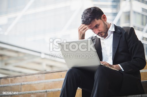 932342408istockphoto Young caucasian businessman feel stressed/worry/headache/disappoint during working on laptop at outdoor office 962067452