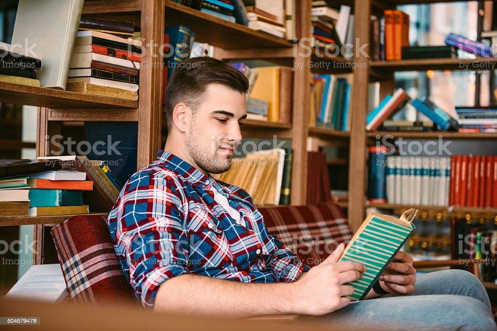 Young Caucasian Casual Man Reading Book In Concept Cafe Library