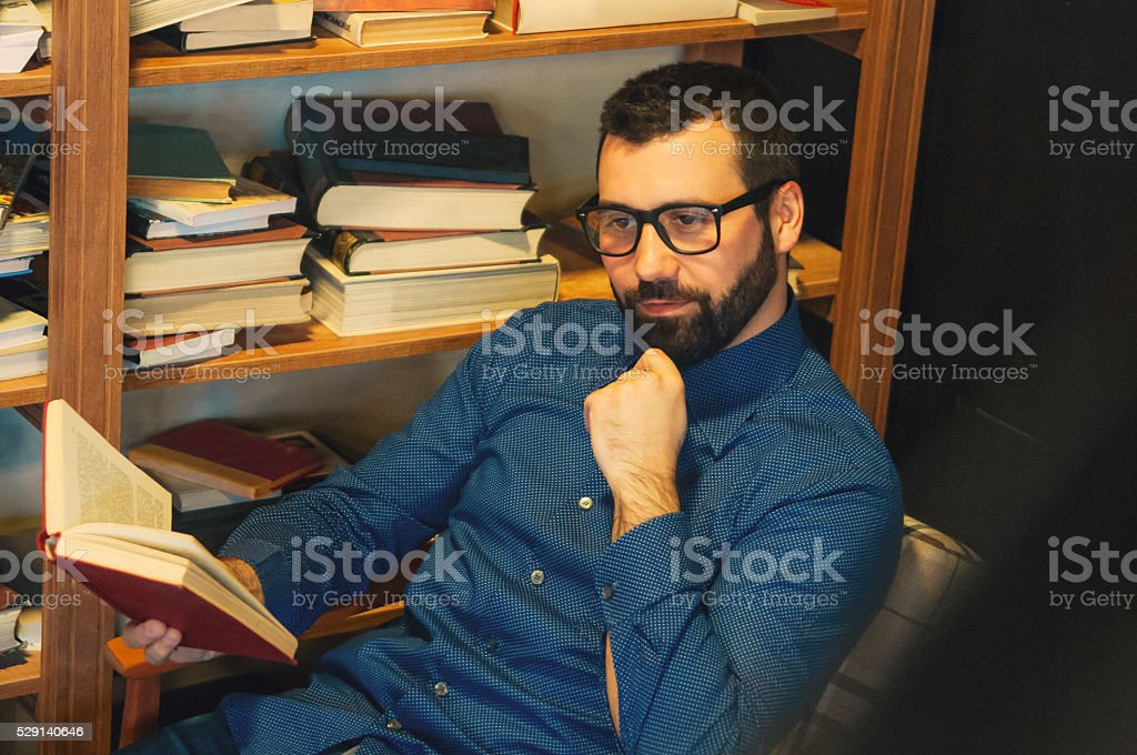 Young Caucasian Casual Man Reading Book In Concept Cafe
