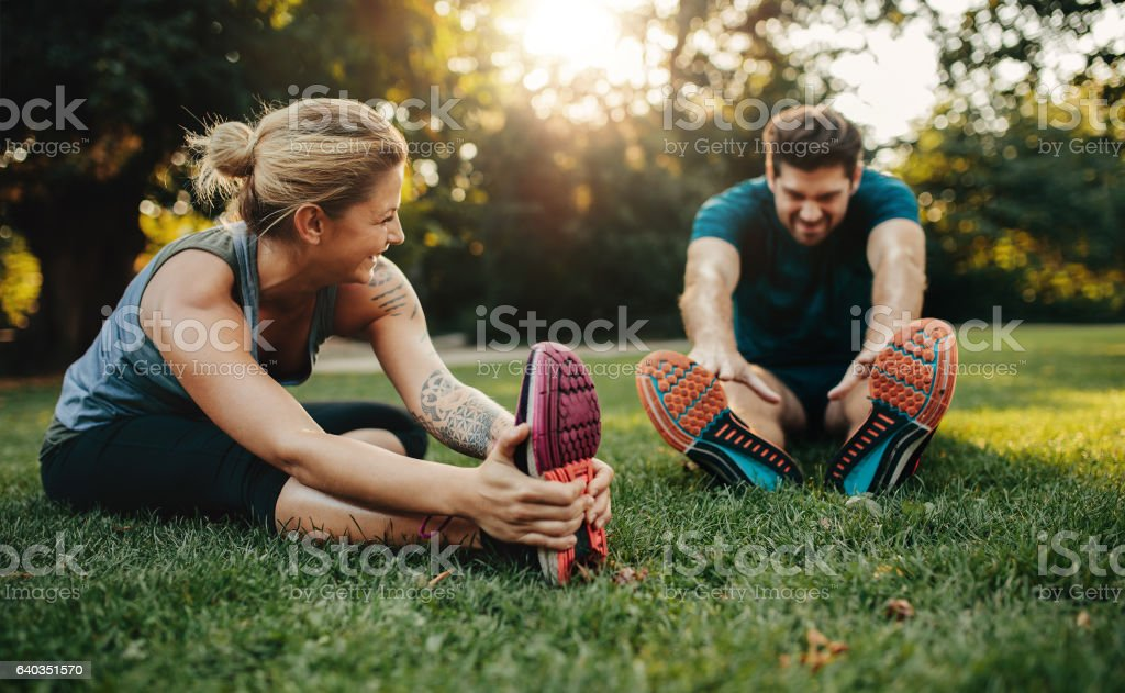 Young caucasian couple exercising in park stock photo