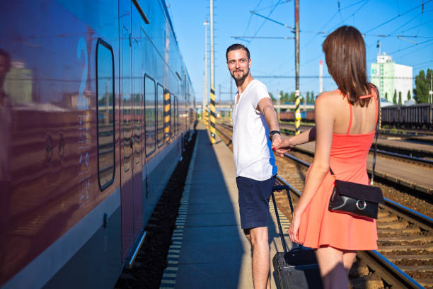 Young caucasian couple holding hands at train station, walking next to the train, wearing casual summer clothes Young caucasian couple holding hands, walking next to a train, departure concept. They are wearing casual summer clothes. long distance relationship stock pictures, royalty-free photos & images
