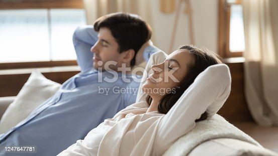 938682762 istock photo Young caucasian couple relax on couch in living room 1247647781