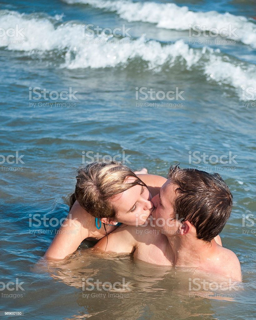 Young Caucasian Couple Romantically Kissing in the Ocean royalty-free stock photo