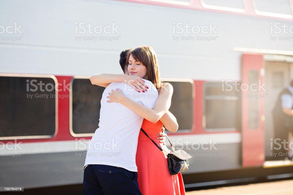 Jeune caucasien couple se tenant à la gare, étreindre pour goodbye - Photo