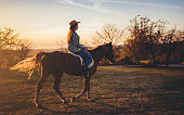 Young caucasian cowgirl riding horse at sunset.