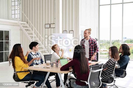 1031237974 istock photo Young caucasian creative man standing and making presentation at modern office happy talking and brainstorming with team. Casual multiethnic diverse people business meeting concept with rear view. 1006991594