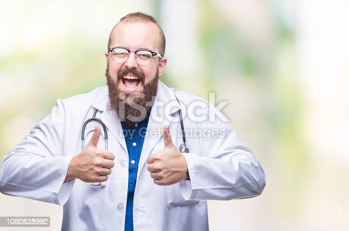 Young caucasian doctor man wearing medical white coat over isolated background success sign doing positive gesture with hand, thumbs up smiling and happy. Looking at the camera with cheerful expression, winner gesture.