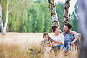 Young Caucasian family sitting under the tree in field