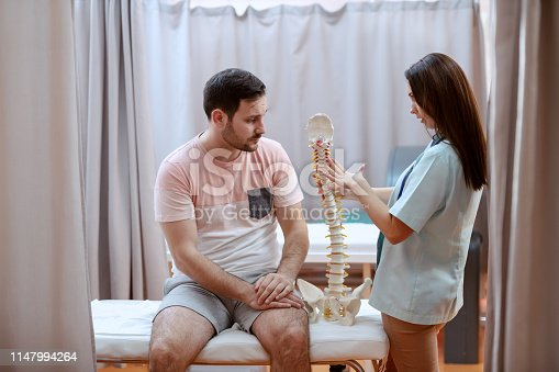 609830806 istock photo Young Caucasian female doctor showing spine model to her male patient. 1147994264