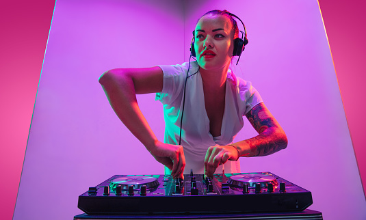 Summertime. Young female musician in headphones performing on purple background in neon light. Concept of music, hobby, festival, entertainment, emotions. Joyful party host, DJ, portrait of artist.
