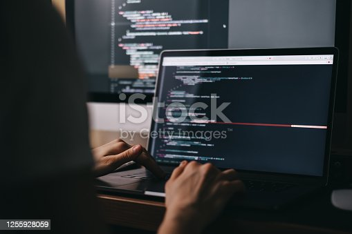 Young caucasian female programmer in glasses writes program code on a laptop computer. home office. High quality photo