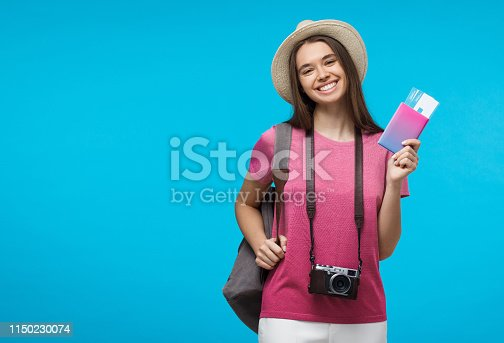 Young Caucasian female ready to go on journey with plane tickets and retro camera, isolated