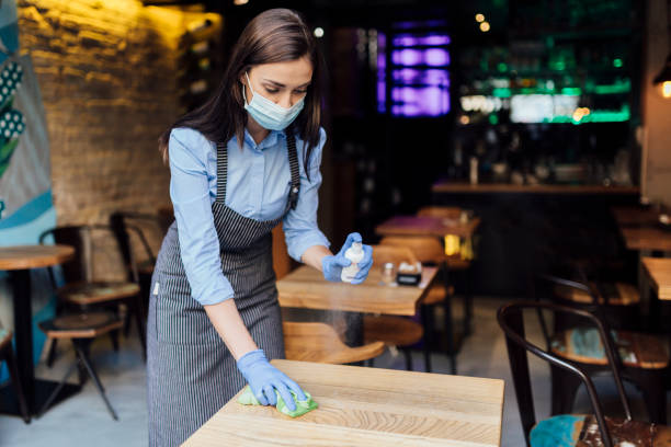 Young Caucasian female waitress cleaning the tables stock photo