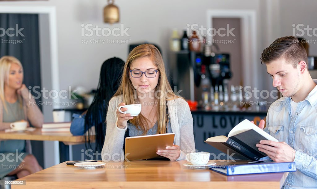 Young caucasian friends  studying at a coffee shop royaltyfri bildbanksbilder