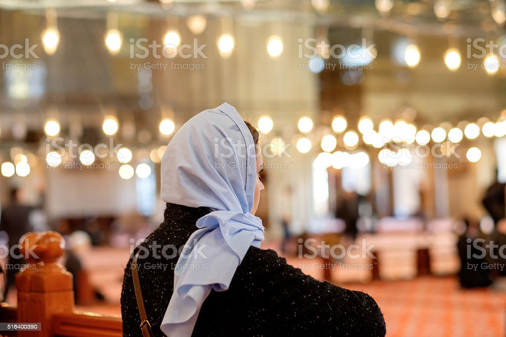 Young caucasian girl a headscarf in the mosque stock photo