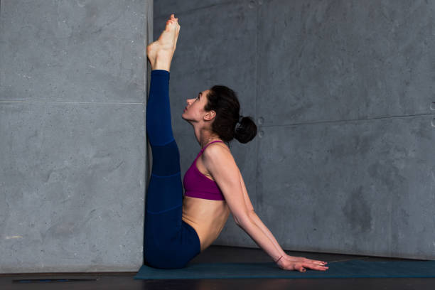 Young Caucasian girl doing upward facing forward bend exercise against the wall during yoga class in studio Young Caucasian girl doing upward facing forward bend exercise against the wall during yoga class in studio. hamstring stock pictures, royalty-free photos & images