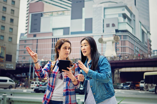 young caucasian girl is lost in japan and asking local mature woman for help - lost stock photos and pictures