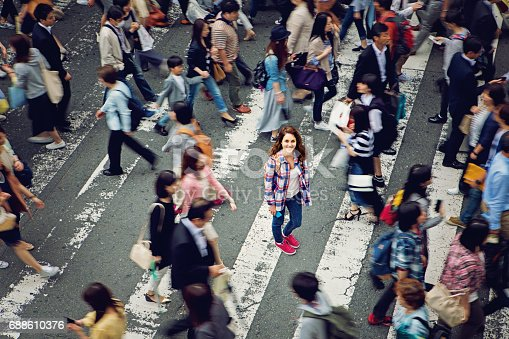 istock Young caucasian girl is smiling confused losted in Tokyo crowd 688610376