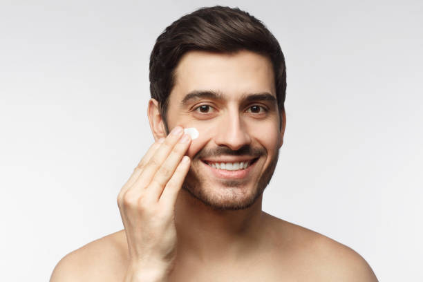 Young Caucasian guy touching face and spreading cream as part of morning selfcare, isolated on gray background Young Caucasian guy touching face and spreading cream as part of morning selfcare, isolated on gray background shirtless male models stock pictures, royalty-free photos & images