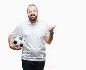 Young caucasian hipster man holding soccer football ball over isolated background pointing and showing with thumb up to the side with happy face smiling