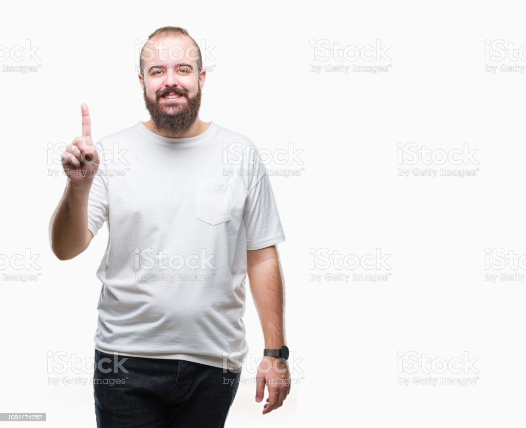 Young caucasian hipster man wearing casual t-shirt over isolated background showing and pointing up with finger number one while smiling confident and happy. stock photo