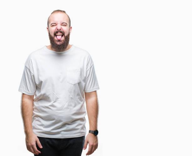 junge hipster kaukasischen mann mit lässigen t-shirts über isolierte hintergrund zunge heraus glücklich mit lustigen ausdruck. emotion-konzept. - ausgefallene mode für mollige stock-fotos und bilder