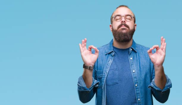 junge hipster kaukasischen mann mit brille über isolierte hintergrund entspannen und lächelnd mit augen geschlossen meditation geste mit den fingern zu tun. yoga-konzept. - mann bart freisteller stock-fotos und bilder