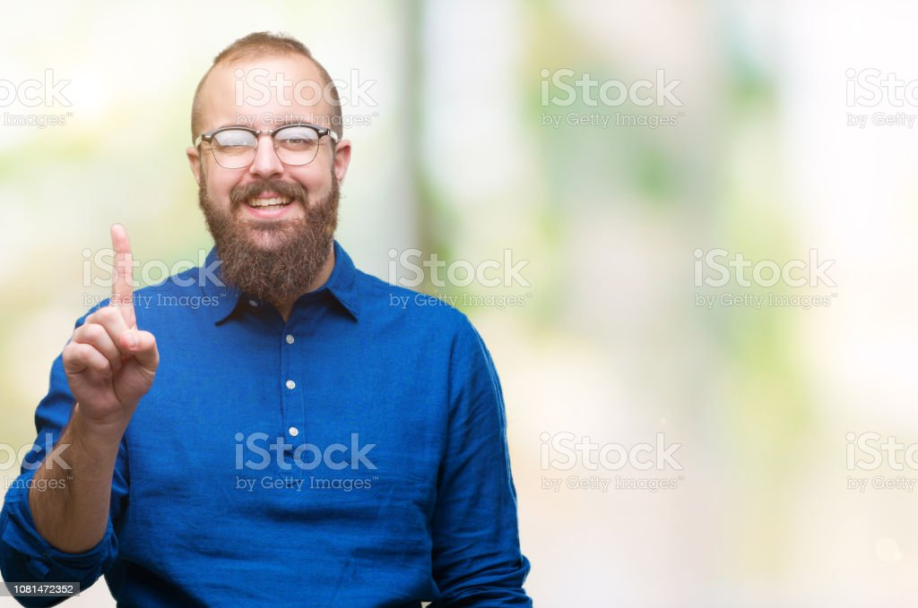 Young caucasian hipster man wearing glasses over isolated background showing and pointing up with finger number one while smiling confident and happy. stock photo