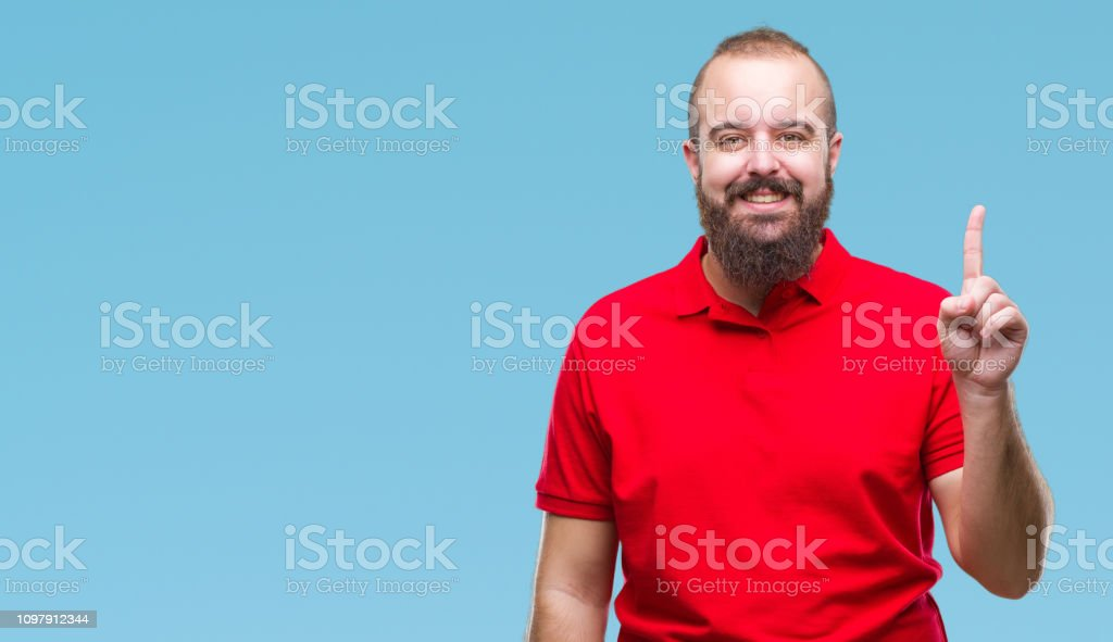 Young caucasian hipster man wearing red shirt over isolated background showing and pointing up with finger number one while smiling confident and happy. stock photo