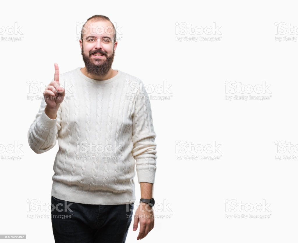 Young caucasian hipster man wearing winter sweater over isolated background showing and pointing up with finger number one while smiling confident and happy. stock photo