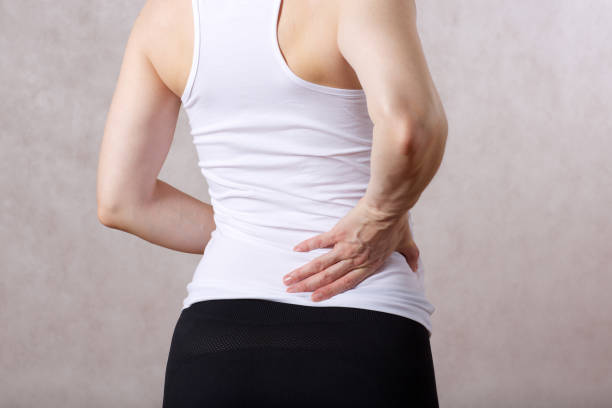 Young caucasian lady between 30 and 40 years has a pain in her back. stock photo