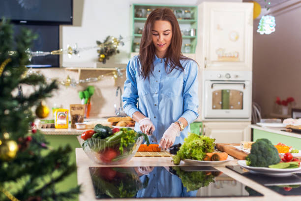 young caucasian lady cooking new year or christmas meal in decorated kitchen at home - christmas cooking imagens e fotografias de stock