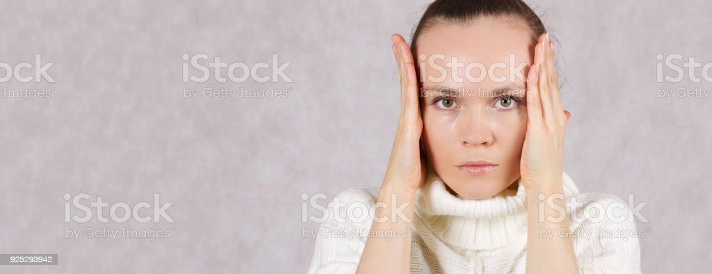 Young caucasian lady uses her palms as blinders. stock photo