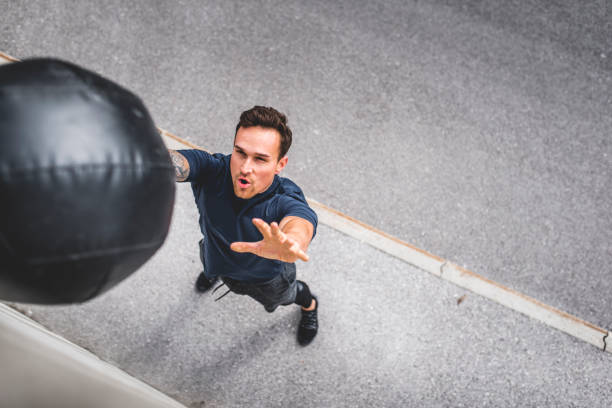 Young Caucasian Male Athlete Doing Medicine Ball Wall Throw stock photo
