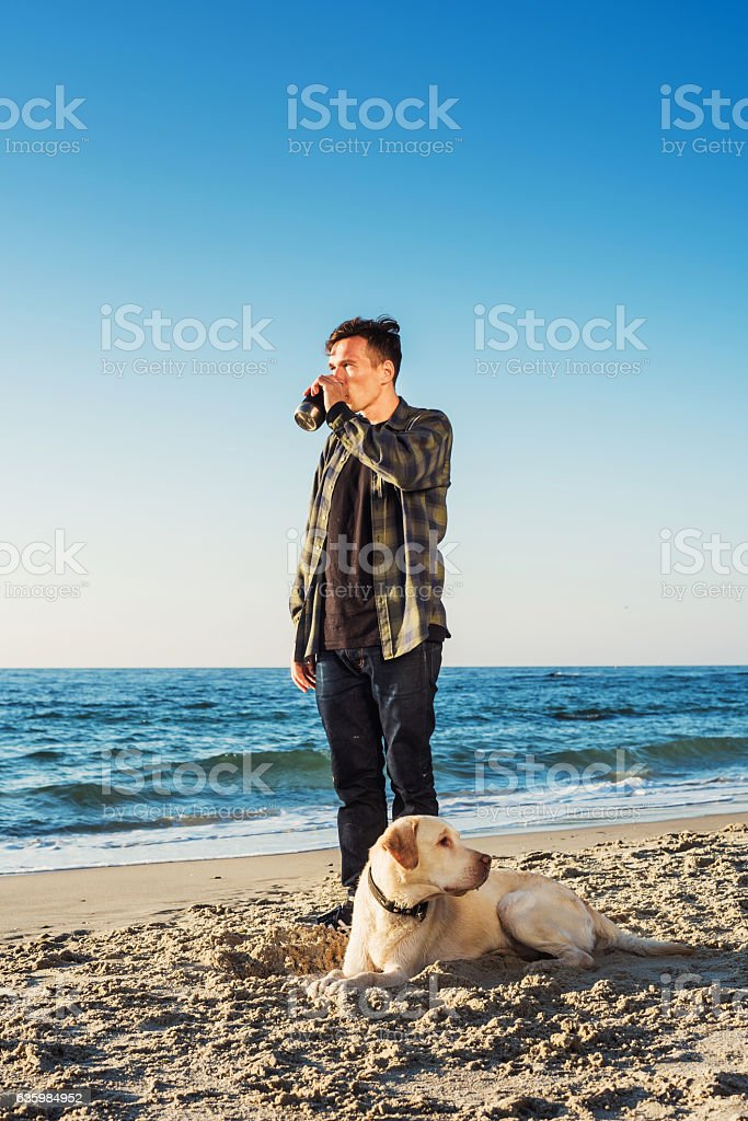 young caucasian male drinking coffee on beach, walking with dog stock photo